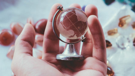 Cupped hands holding a small globe