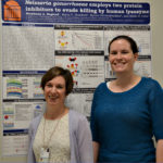 Researchers A. Criss, PhD and S. Ragland, PhD standing in front of their research poster